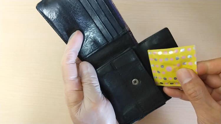 財布の中にコンドームを入れるようす